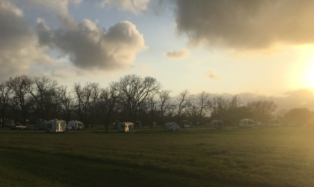 View of back of large grassy area in front of campsites at Thousand Trails in Columbus, Texas